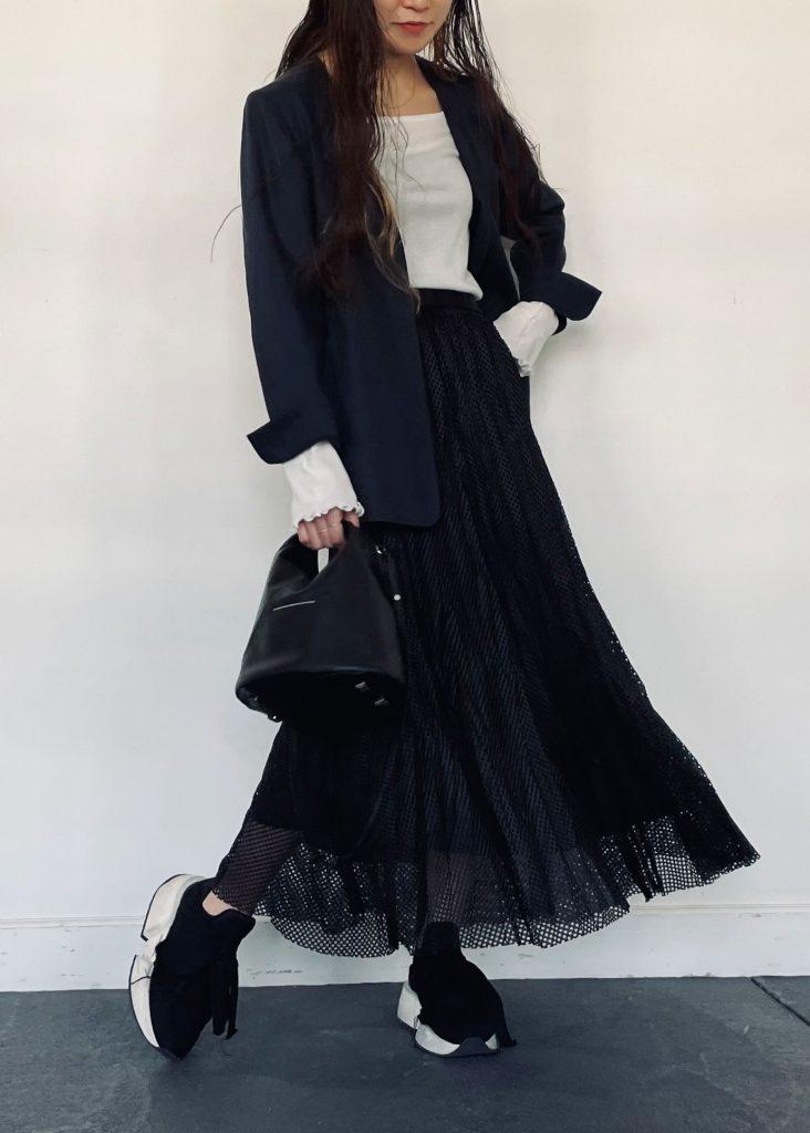 シンプルなホワイトカラーの長袖トップスに綿麻ノーカラージャケットを羽織ったきっちりコーデ。ボトムスはメッシュ素材がポイントのスカートを合わせコーデのポイントに。