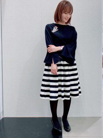 ブラックのフレアスリーブコットンカットソーにボーダースカートとタイツを合わせたコーディネート。