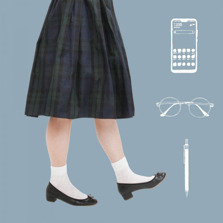 タータンチェックのスカートは白い靴下とヒール付きの黒バレエシューズで賢い系女子を演出。