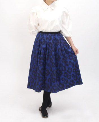サテン地に花柄のジャガードをプラスしたネイビーのミモレ丈スカート。ホワイトのボリュームスリーブコットンシャツを合わせた秋冬コーディネートです。