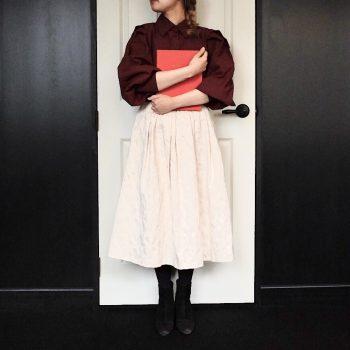 サテン地に花柄のジャガードをプラスしたホワイトのミモレ丈スカート。ワインのボリュームスリーブコットンシャツを合わせた秋冬コーディネート。上品で大人かわいいを演出してくれます。