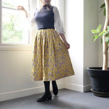 サテン地に花柄のジャガードをプラスしたイエローのミモレ丈スカート。光沢控えめなスカートで秋冬コーデにも馴染み、またコーディネートのポイントになります♪