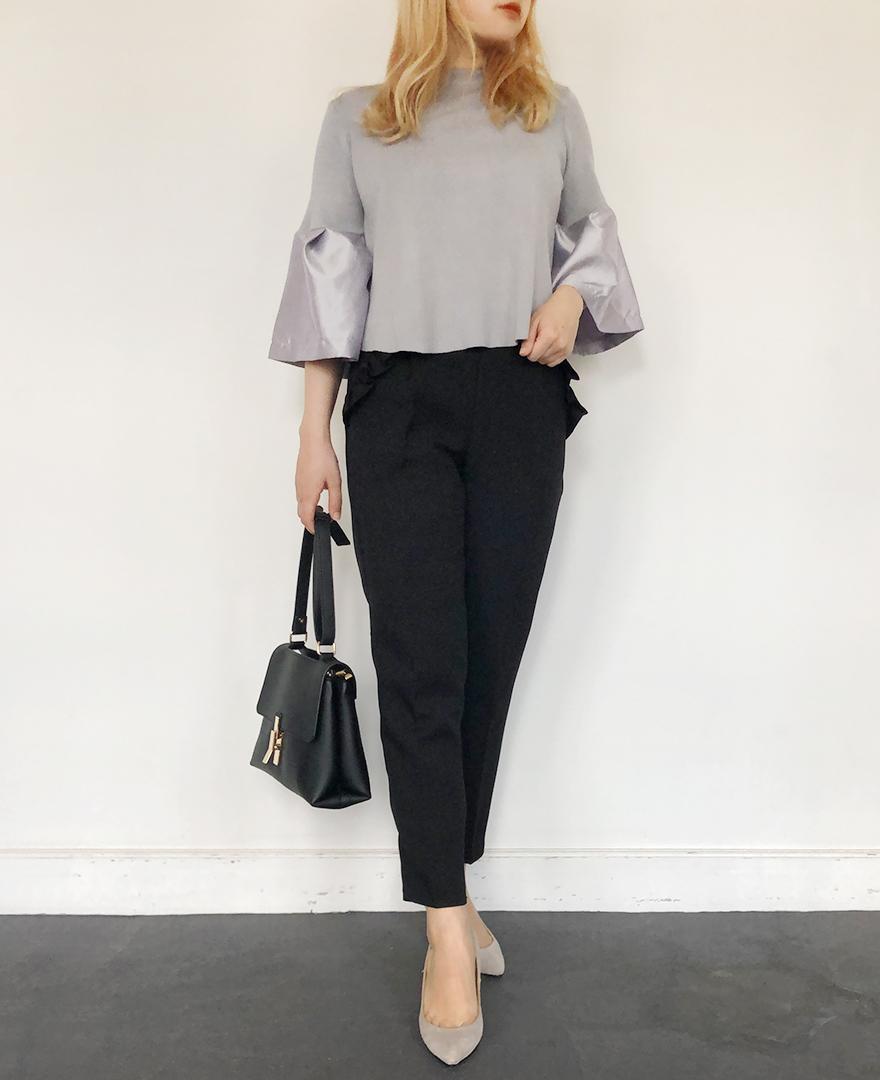 グレーのラッパ袖プルオーバー ブラックの神戸山の手ポケットフリルパンツ グレーの7cmヒールパンプス ブラックのきれいめバッグ