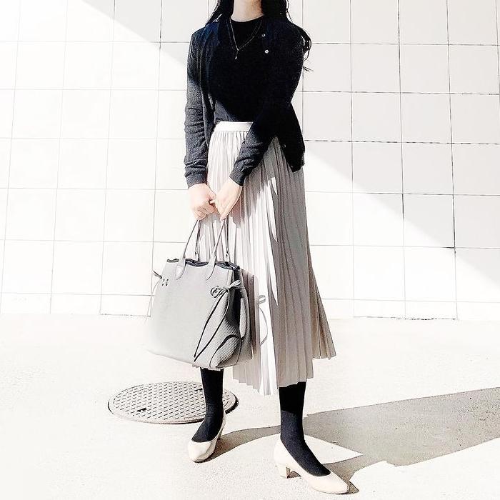 ベージュのプリーツスカート、ベージュのバッグにはカラーリンクでベージュのパンプスを合わせます