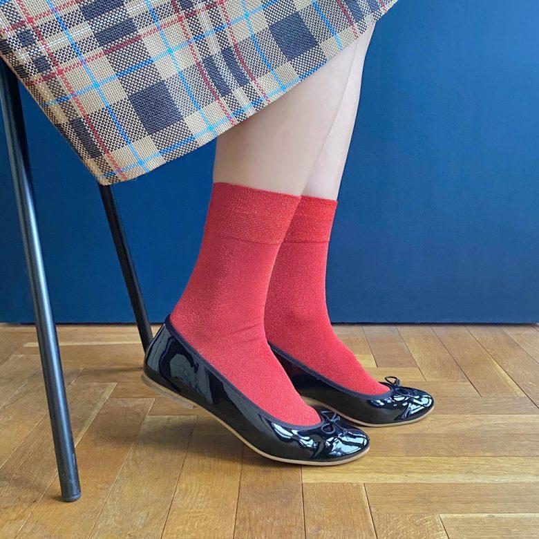 トラッなチェック柄のスカートに黒のエナメルバレエ、差し色に赤い靴下を合わせたコーディネート。