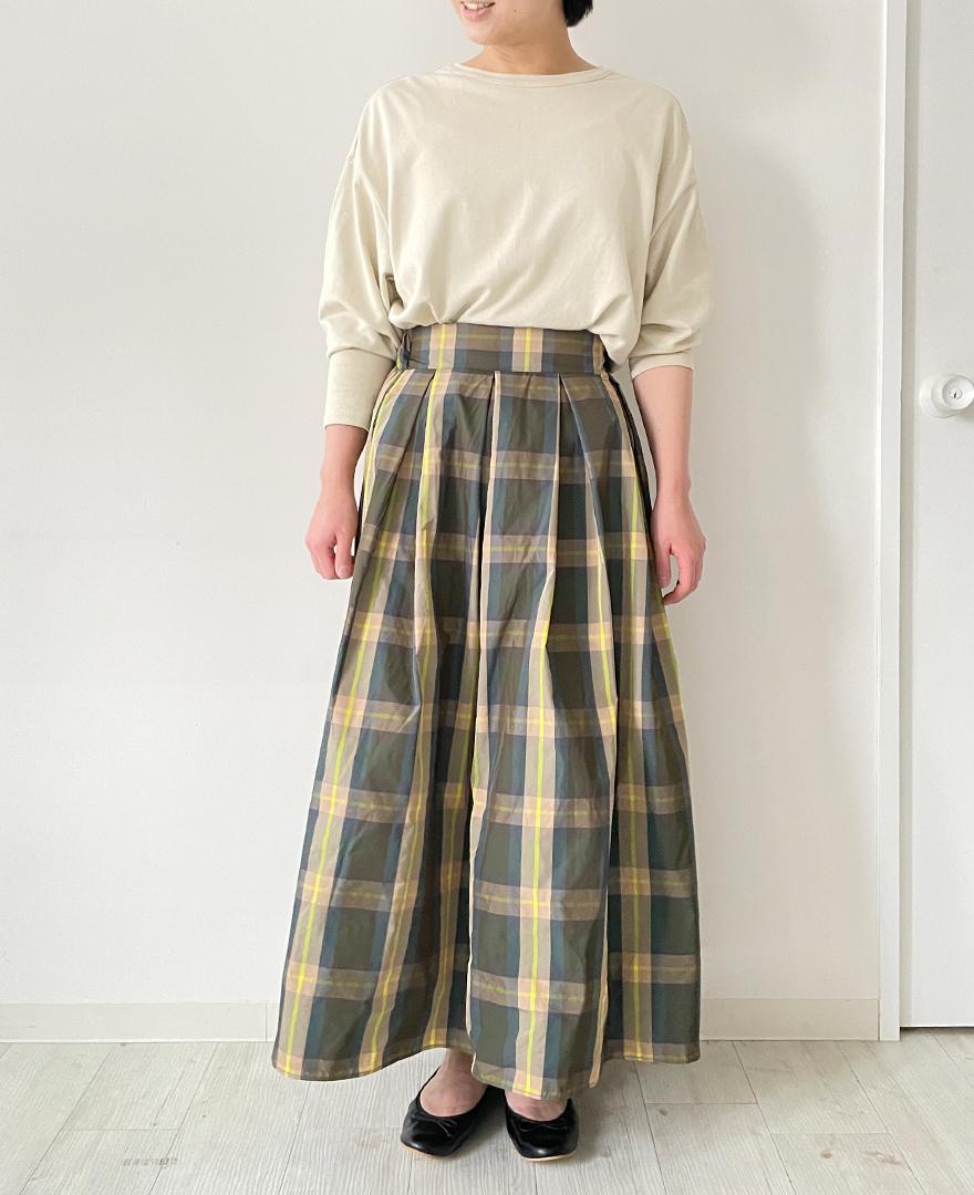 ベージュの長袖トップスにイエローのチェック柄スカートをコーディネート。