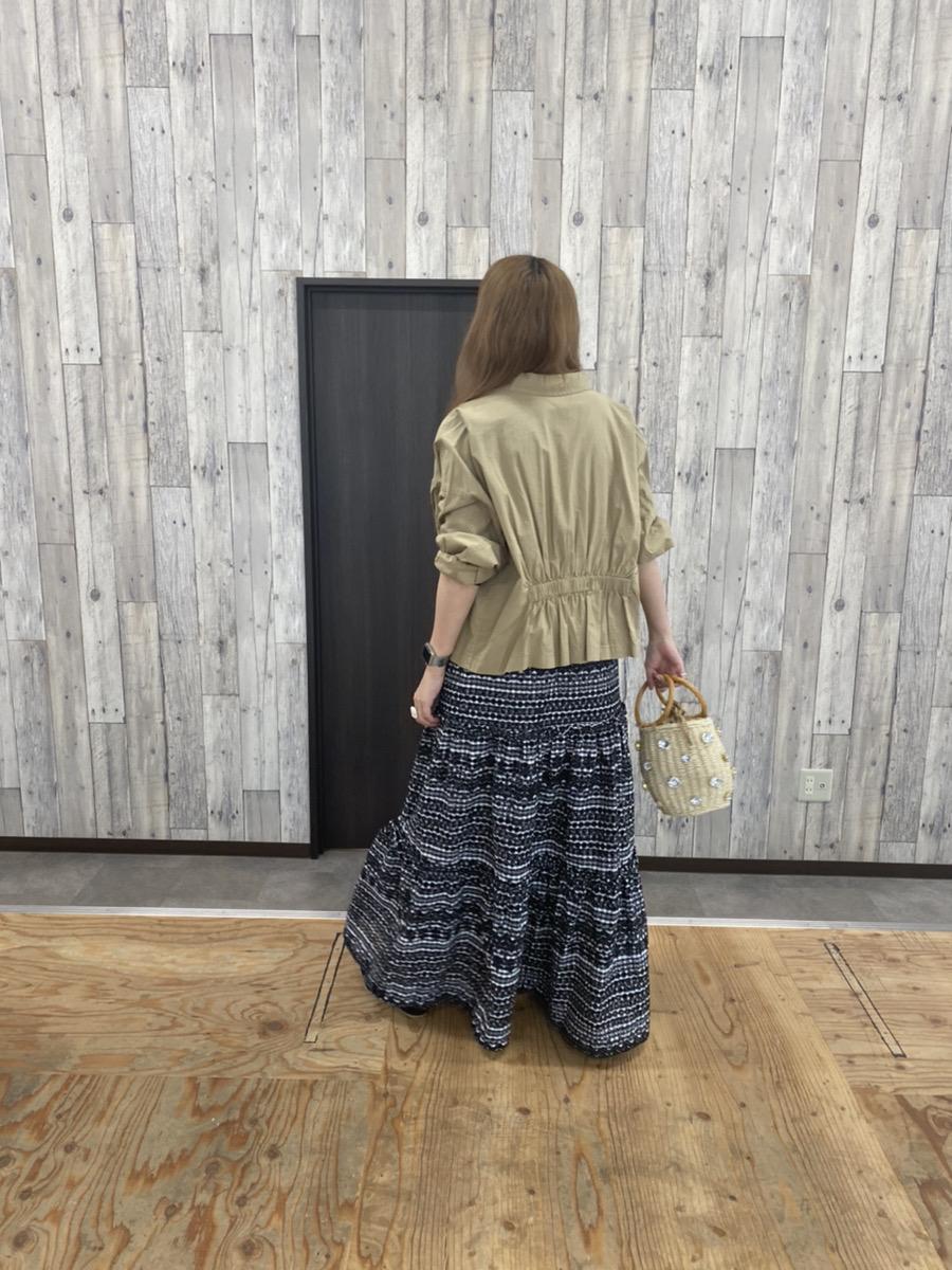 ベージュのジャケットとパンチングスカートのコーディネート(後ろ姿)
