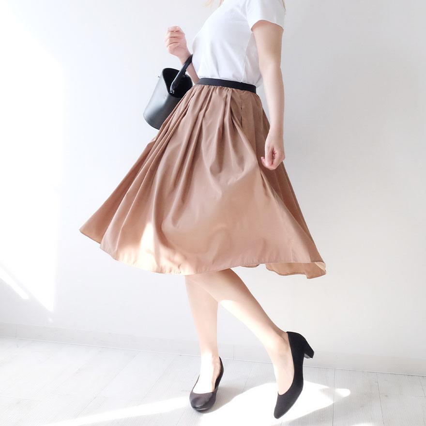 シナモンカラーのフレアスカートを着用した女性