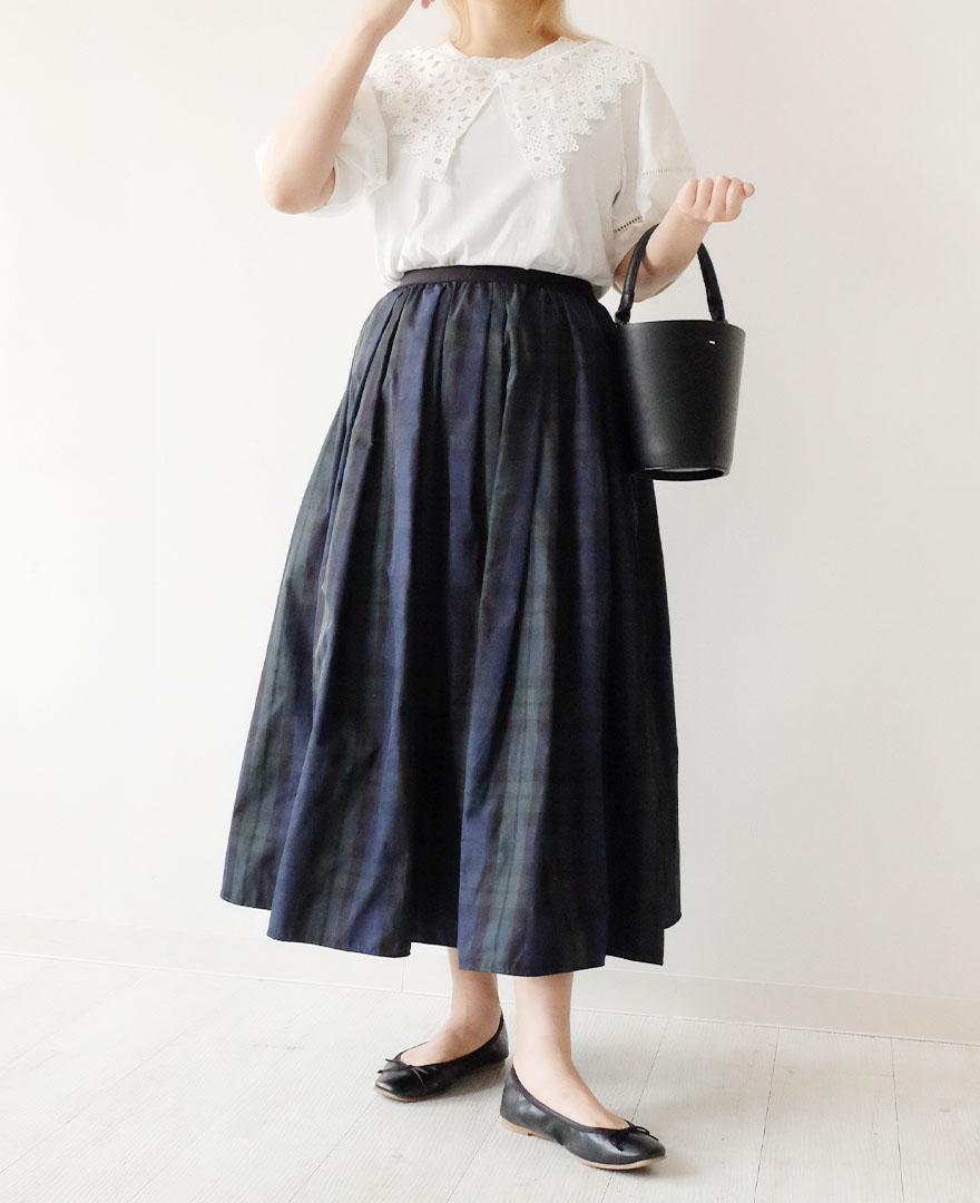 大きいレースの襟がついたホワイトのTシャツに、タータンチェックのマキシ丈スカートをコーディネート