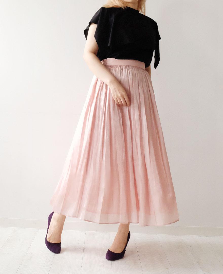 ブラックのケープデザイントップスにピンクのマキシスカートをコーディネート