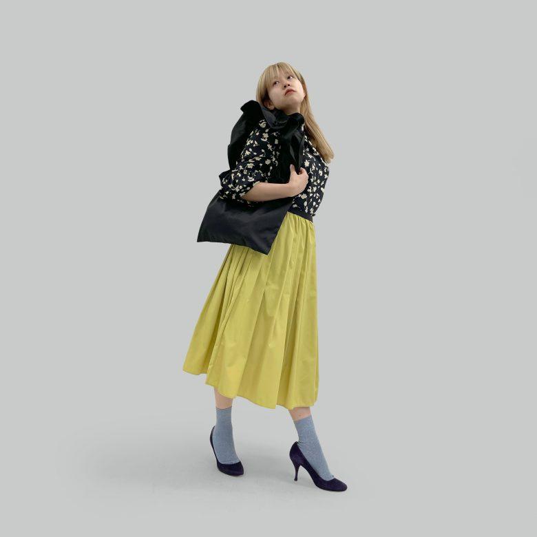 ミモザの山の手スカートにブラックのボタニカルブラウスとブルーのソックスを合わせて上品だけどポップなコーディネートに