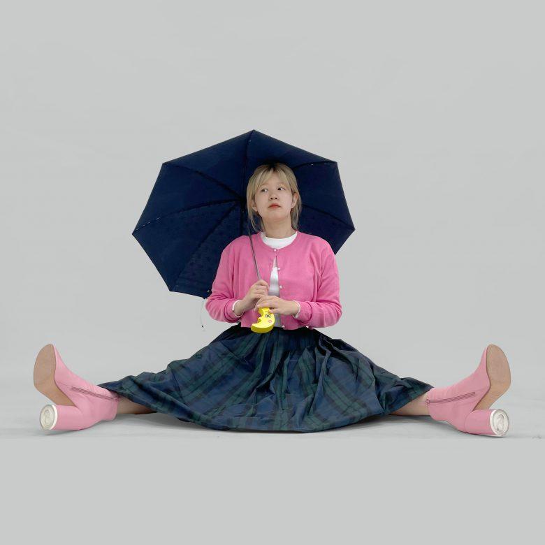 タータンチェックのスカートにピンクのニットとブーツを合わせてキュートなコーディネートに